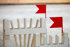 Closeup white obstacle with red flag for jumping horses. Riding competition. Royalty Free Stock Image