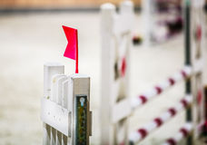 Closeup white obstacle with red flag for jumping horses. Riding competition. Royalty Free Stock Photos