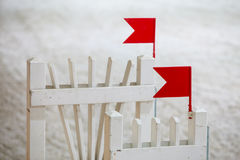 Closeup white obstacle with red flag for jumping horses. Riding competition. Royalty Free Stock Photo