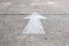 Closeup white painted arrow sign on cement street floor background Royalty Free Stock Photos