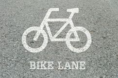 Closeup white painted of bicycle sign in bike lane at the street floor in park textured background