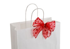 Closeup of white paper gift bag with red bow Royalty Free Stock Photo