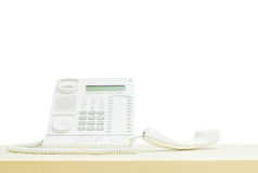 Closeup white phone , office phone on blurred wooden desk in the meeting room under window light isolated on white background Stock Photo