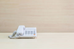 Closeup white phone , office phone on blurred wooden desk and wall textured background in the meeting room under window light Royalty Free Stock Photos