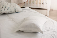 Closeup of white pillow on untidy bed at sunny day Royalty Free Stock Photography