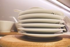 White plates and dinnerware display on shelf. Closeup of white plates and dinnerware display on shelf stock photo