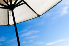 Closeup of white resort umbrella against blue sky Royalty Free Stock Image
