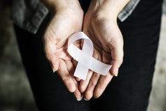 Closeup of white ribbon on hands palm bone cancer anti violence awareness stock photo