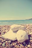 Closeup of white stones on the pebbly beach; filtered, faded, retro style. Closeup of white stones on the pebbly beach, on a sunny day. Image filtered in faded Royalty Free Stock Image