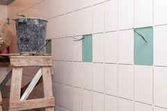 Closeup white tile on the wall of drywall without grout and electrical wires, scaffold, bucket with adhesive. Concept of repair in royalty free stock photo