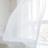 Closeup of white waving curtain in bedroom royalty free stock photo