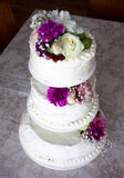 Closeup of white wedding cake with brown ribbon and flowers on top. Royalty Free Stock Photos