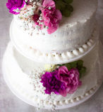 Closeup of white wedding cake with brown ribbon and flowers on top. Stock Photography
