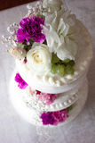 Closeup of white wedding cake with brown ribbon and flowers on top. Royalty Free Stock Photography