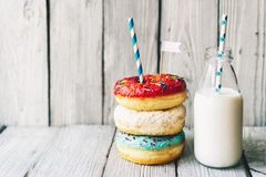 Several glazed cream donuts and milk in a bottle stock photography
