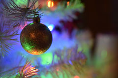 Closeup of a white xmas tree with a gold colored decoration ball Royalty Free Stock Images