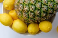 Closeup of whole fresh pineapple textrued skin with lemons Royalty Free Stock Image