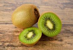 Closeup whole and sliced kiwi fruit on wood table Stock Photo