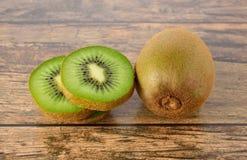 Closeup whole and sliced kiwi fruit on wood table Royalty Free Stock Image