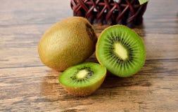 Closeup whole and sliced kiwi fruit on wood table Stock Photos