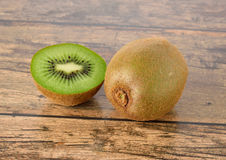 Closeup whole and sliced kiwi fruit on wood table Stock Photos