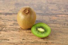 Closeup whole and sliced kiwi fruit on wood table Stock Photography