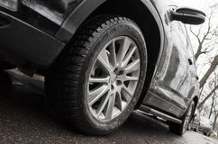 Closeup wide angle photo fragment of black car. Light alloy wheel with winter tires on dirty city road. Selective focus and shallow DOF Royalty Free Stock Images
