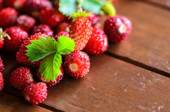 Closeup of wild strawberries on wooden table Stock Photos