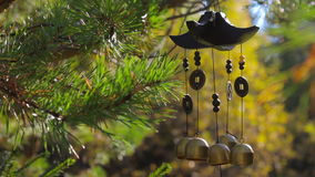 Closeup wind chimes swaying in the wind at autumn garden. With sound stock footage