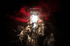 Closeup wine glass with fog at dark background. Beautiful glass with smoke and light. Selective focus stock images