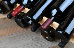 Closeup of a Wine Rack. Full of bottles on a rustic wooden table Royalty Free Stock Photos