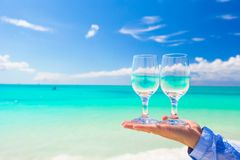 Closeup of wineglasses in hand on the white sandy Stock Photography