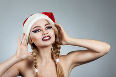 Closeup winter portrait of girl in santa hat. Bright creative makeup. Royalty Free Stock Image