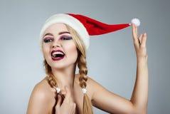 Closeup winter portrait of girl in santa hat. Bright creative makeup. Stock Photos