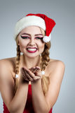 Closeup winter portrait of girl in santa hat. Bright creative makeup. Stock Image