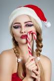 Closeup winter portrait of girl in santa hat. Bright creative makeup. Positive emotions Stock Image