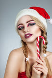 Closeup winter portrait of girl in santa hat. Bright creative makeup. Positive emotions Stock Images