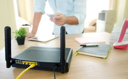 Closeup of a wireless router and a man using smartphone on livin Stock Image