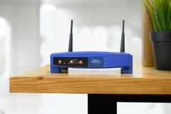 Closeup of a wireless router and a man using smartphone on living room at home ofiice stock photo