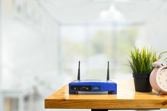Closeup of a wireless router and a man using smartphone on living room at home ofiice stock photography