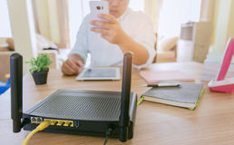 Closeup of a wireless router and a man using smartphone on living room at home ofiice Stock Images