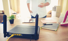 Closeup of a wireless router and a man using smartphone on living room at home ofiice Royalty Free Stock Images