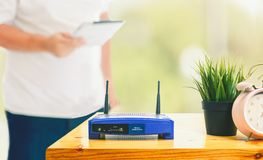Closeup of a wireless router and a man using smartphone on living room at home ofiice royalty free stock photo