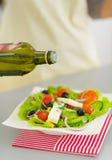 Closeup on woman adding oil into salad Royalty Free Stock Photo