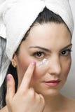 Closeup woman applying cream face stock photos