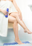 Closeup of woman applying moisturizing creme after shaving legs Stock Image