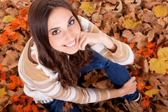 Closeup of a woman in autumn leaves royalty free stock photos