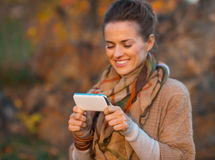 Closeup on woman in autumn  outdoors writing sms Royalty Free Stock Photos