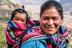 CLOSEUP OF WOMAN WITH BABY IN PERUVIAN ANDES. URUBAMBA, CUSCO, PERU - CIRCA 2015: Portrait of an unidentified woman with baby circa 2015 in Urubamba, Peru royalty free stock image