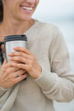 Closeup on woman on beach with cup of hot beverage Royalty Free Stock Photography